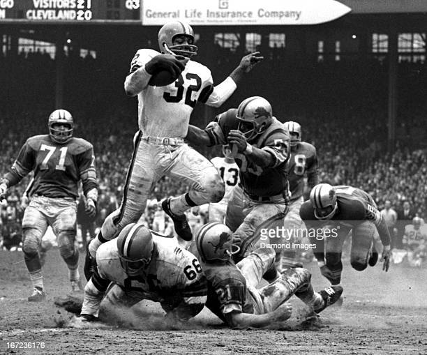 Fullback Jim Brown of the Cleveland Browns runs through the defense during a game on November 15 1964 against the Detroit Lions at Cleveland...
