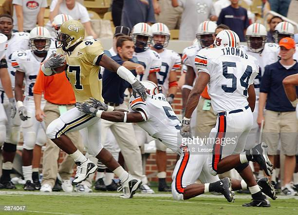 Fullback Jimmy Dixon of the Georgia Tech Yellow Jackets runs down the sideline past linebacker Travis Williams of the Auburn Tigers during the game...