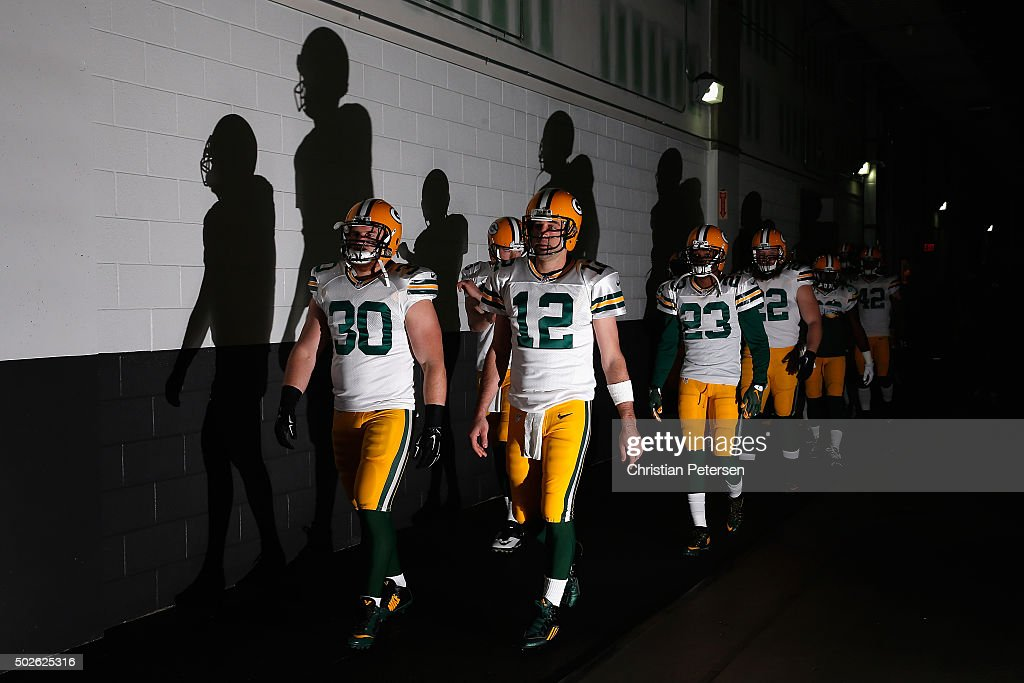 Fullback John Kuhn #30 and quarterback Aaron Rodgers #12 of the Green Bay Packers walk out with their team to the field prior to the NFL game against the Arizona Cardinals at the University of Phoenix Stadium on December 27, 2015 in Glendale, Arizona.