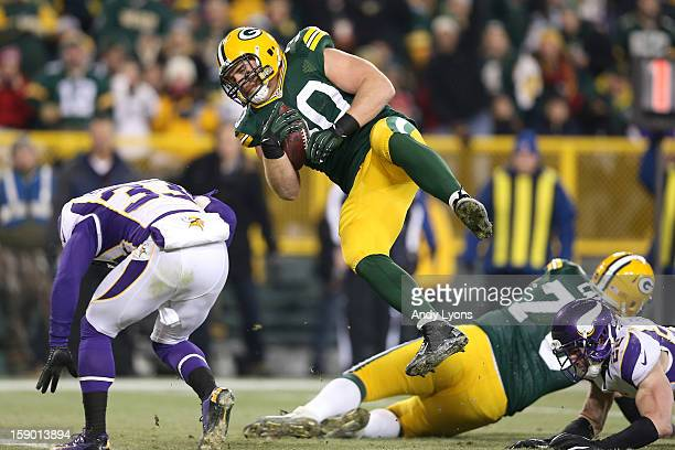 Fullback John Kuhn of the Green Bay Packers flies over safety Jamarca Sanford of the Minnesota Vikings to score on a nine-yard touchdown catch and...