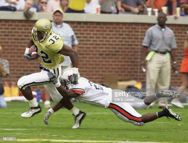 Fullback Johnathan Jackson of the Georgia Tech Yellow Jackets attempts to break out of the tackle from safety Karibi Dede of the Auburn Tigers during...