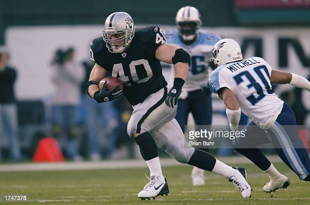 Fullback Jon Ritchie of the Oakland Raiders carries persued by cornerback Donald Mitchell of the Tennessee Titans during the AFC Championship game at...