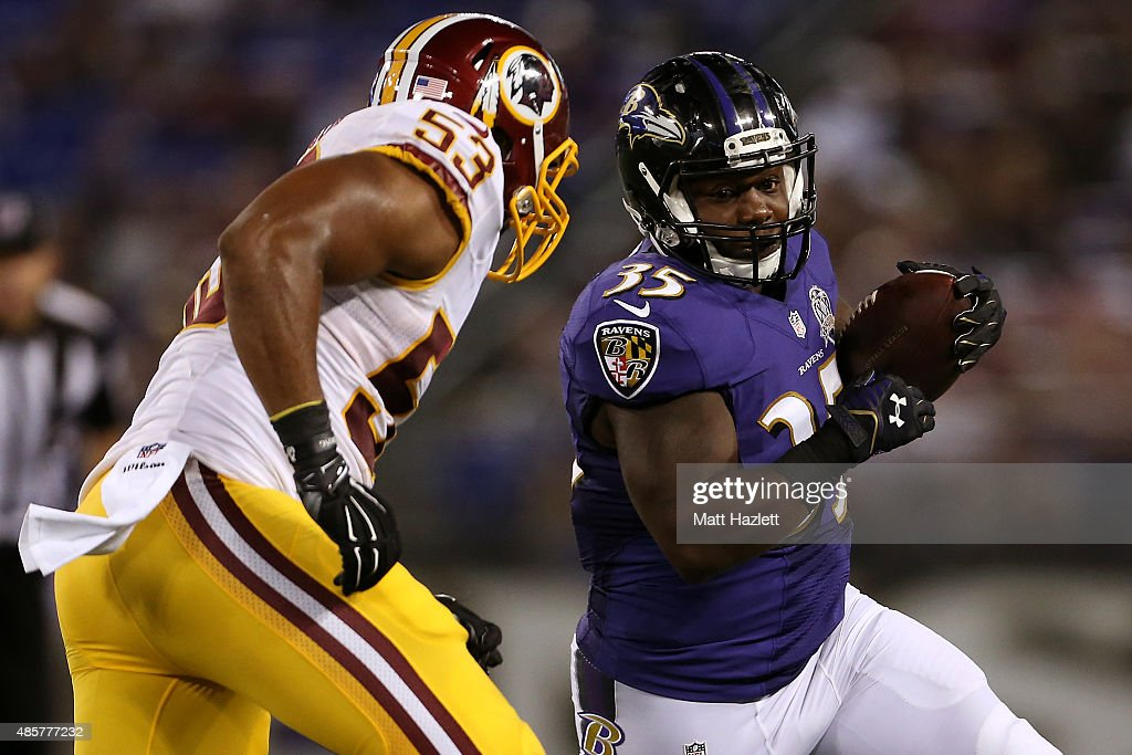 Fullback Kiero Small #35 of the Baltimore Ravens carries the ball while outside linebacker Jackson Jeffcoat #53 of the Washington Redskins defends in the fourth quarter of a preseason game at M&T Bank Stadium on August 29, 2015 in Baltimore, Maryland.