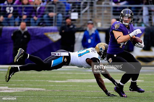 Fullback Kyle Juszczyk of the Baltimore Ravens avoids the tackle of defensive end Chris Clemons of the Jacksonville Jaguars in the second quarter at...