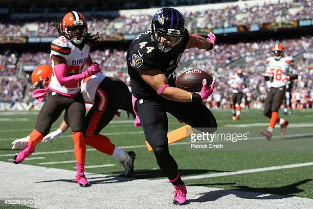 Fullback Kyle Juszczyk of the Baltimore Ravens scores a first quarter touchdown past outside linebacker Paul Kruger of the Cleveland Browns and...