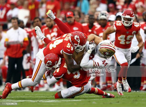 Fullback Kyle Juszczyk of the San Francisco 49ers is tackled by outside linebacker Damien Wilson and Herb Miller of the Kansas City Chiefs during the...