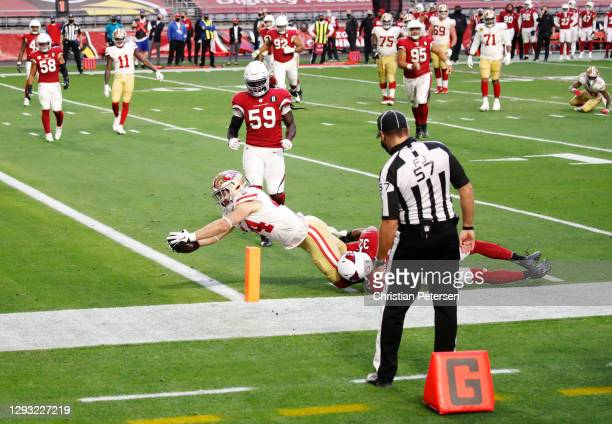 Fullback Kyle Juszczyk of the San Francisco 49ers scores a touchdown as safety Budda Baker of the Arizona Cardinals defends during the second half at...