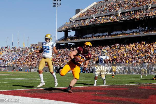 Fullback Mark Cosgrove of the Arizona State Sun Devils scores a touchdown over defensive back Nate Meadors of the UCLA Bruins during the first half...