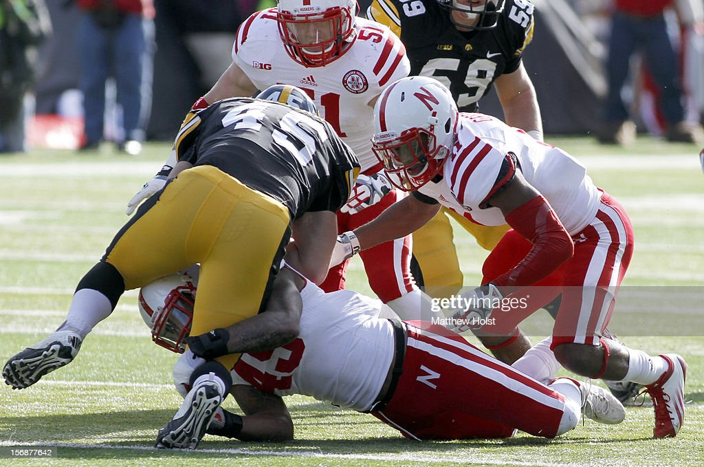 Fullback Mark Weisman #45 of the Iowa Hawkeyes is brought down during the first quarter by linebacker Alonzo Whaley #45, cornerback Andrew Green #11 and linebacker Will Compton #51 of the Nebraska Cornhuskers on November 23, 2012 at Kinnick Stadium in Iowa City, Iowa. Nebraska defeated Iowa 13-7.
