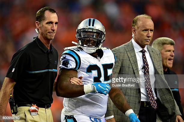 Fullback Mike Tolbert of the Carolina Panthers is helped off the field with an injury against the Denver Broncos at Sports Authority Field at Mile...