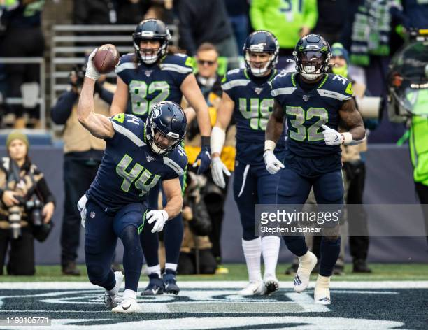 Fullback Nick Bellore of the Seattle Seahawks spikes the ball after while celebrating with teammates Jacob Hollister, Shaquem Griffin and Chris...