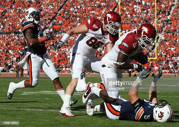 Fullback Van Stumon of the Arkansas Razorbacks runs over linebacker Jake Holland of the Auburn Tigers while tight end Garrett Uekman of the Arkansas...