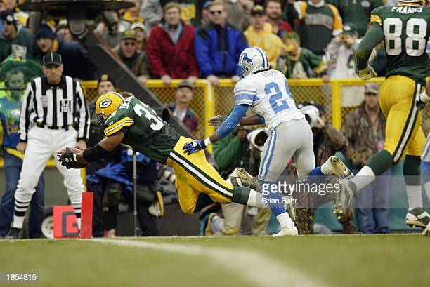 Fullback William Henderson of the Green Bay Packers scores a touchdown in front of cornerback Todd Lyght of the Detroit Lions during the NFL game at...