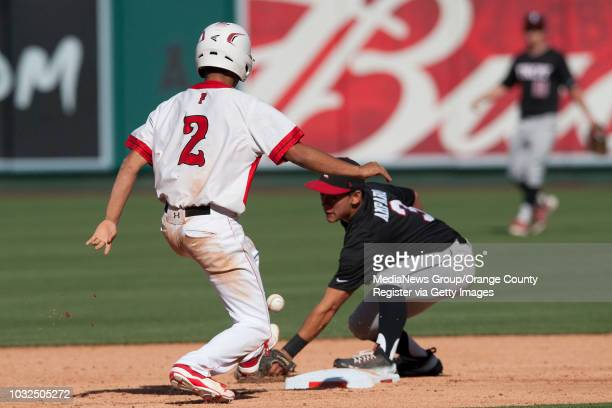 Fullerton's Kai Alporque gets back to second as Troy's Kris Amparo tries to corral the throw during the Indians' 10 victory over Troy High at Angel...