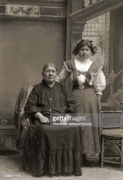 Fulllength atudio portrait in front of a painted backdrop of Lucy Goodvillage Blowsnake sitting beside her granddaughter Nina Thunder Decorah Green...