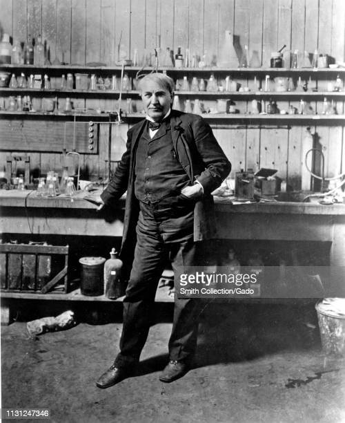 Full-length frontal view of American inventor Thomas Edison, standing in front of a beaker lined work area in his lab, Menlo Park, New Jersey, 1880....
