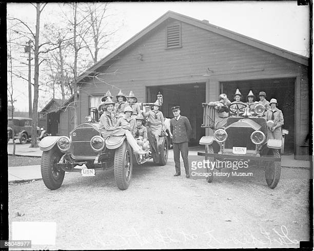 Fulllength group portrait of a group of Girl Scouts sitting and standing on two large automobiles in front of a building at Great Lakes Naval...