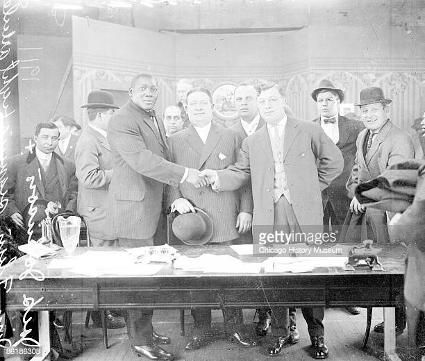 Fulllength group portrait of African American pugilist Jack Johnson wearing a suit standing with Al Tearny and Jim Flynn behind a table covered with...