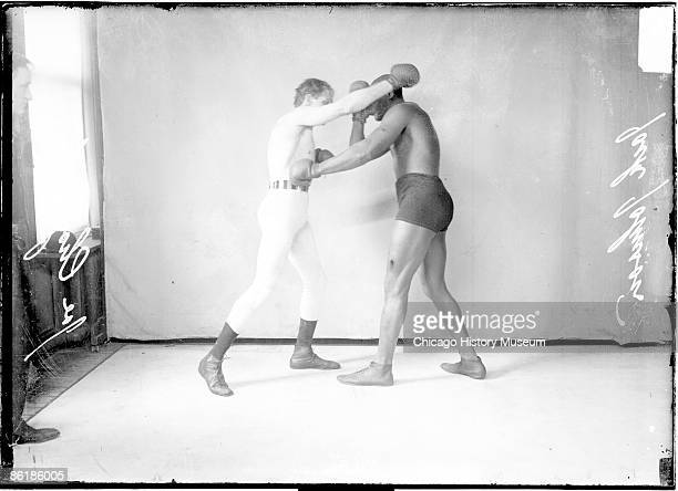 Fulllength group portrait of Jack Johnson African American pugilist throwing a left jab to the body of pugilist Joe Choynski standing in front of a...