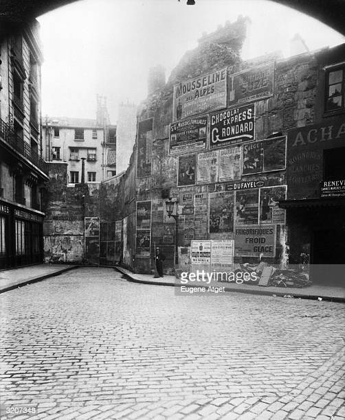 Fulllength image of a street cleaner standing on a sidewalk with a broom in front of a wall covered in poster advertisements rue BriseMiche Paris...