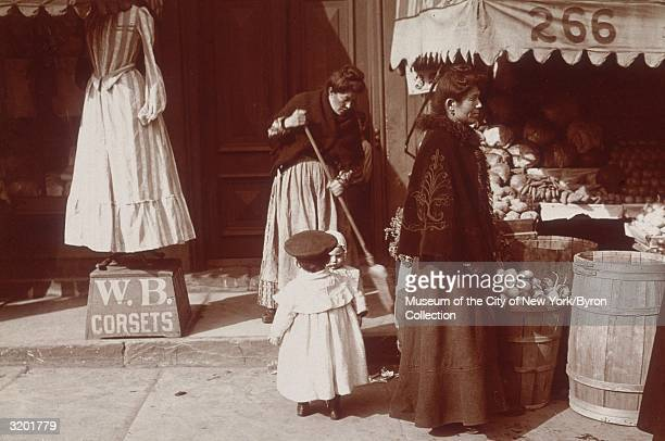 Full-length image of a woman and two young children standing on a sidewalk between a produce store and a corset maker's shop, while another woman...