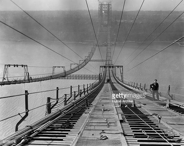 Fulllength image of a worker pausing near the top of the George Washington Bridge during its construction New York City