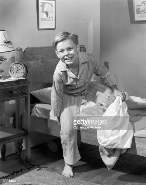 Fulllength image of a young boy smiling as he steps out of bed wearing his pajamas An alarm clock sits on his bedside table