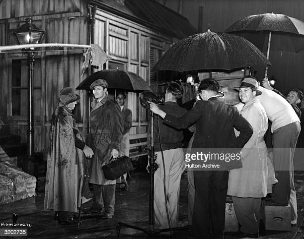 Fulllength image of actors DJ Williams and Robert Donat speaking while director King Vidor looks over his shoulder and smiles on the set of his film...