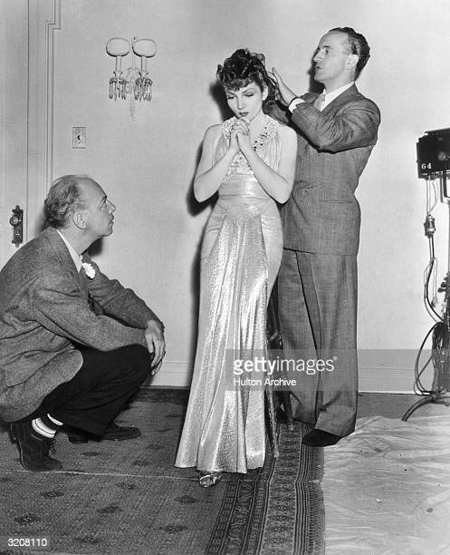 Full-length image of American actor Claudette Colbert standing and having her hair groomed, as American film director Mitchell Leisen crouches and...