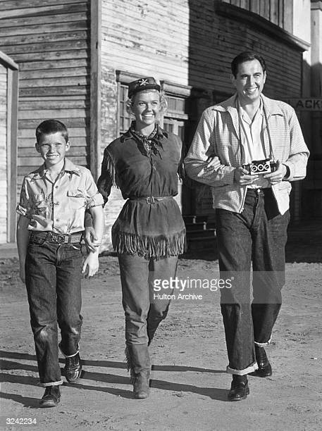 A fulllength image of American actor Doris Day walking with her son Terry and her husband Marty Melcher who is holding a Stereo Realist camera during...