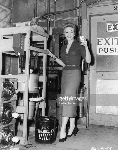 Fulllength image of American actor Kim Novak standing by a water cooler on the set of director George Sidney's film 'The Eddy Duchin Story' She wears...