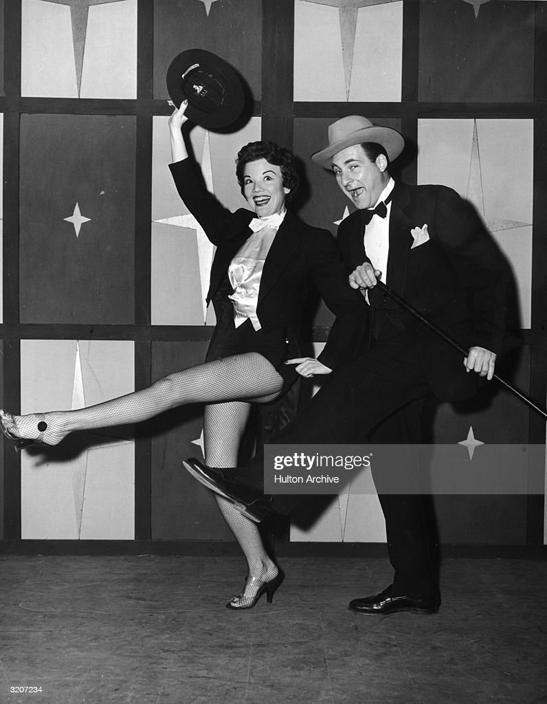 Full-length image of American actors Nanette Fabray and Sid Caesar dancing in a still from the television comedy series, 'Caesar's Hour'. Fabray wears tails and fishnet stockings while holding a hat. Caesar wears a tuxedo and carries a cane.