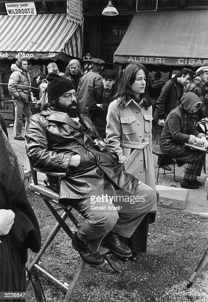 Fulllength image of American film director Francis Ford Coppola sitting in a canvas director's chair outdoors beside his wife Eleanor on the set of...