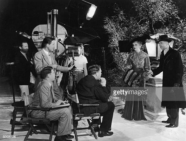 Fulllength image of American film director Robert Z Leonard discussing a scene with American actors Virginia Bruce and William Powell on the set of...
