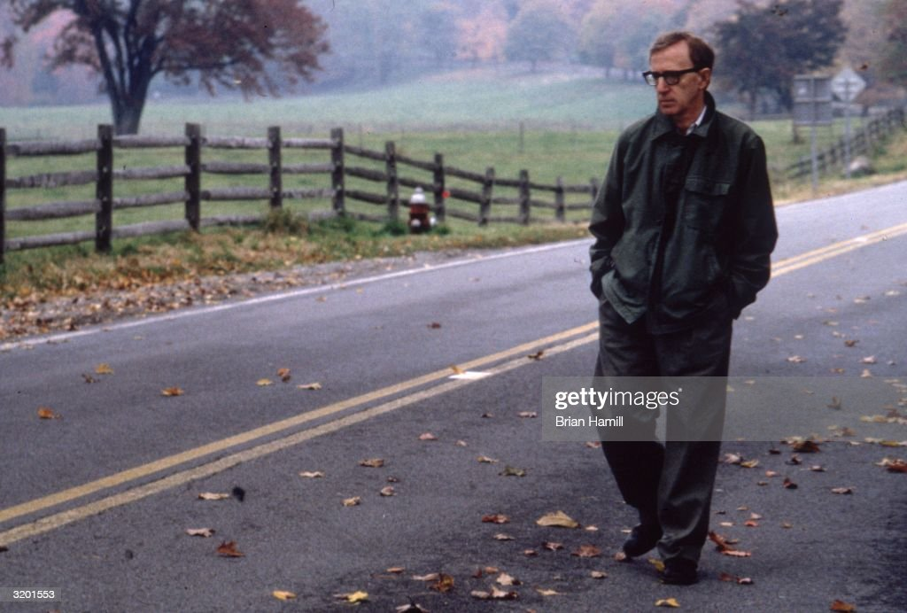 Full-length image of American film director, writer, and actor Woody Allen walking on a country road in a scene from his film, 'Mighty Aphrodite'.