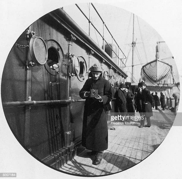 Fulllength image of American inventor manufacturer and philanthropist George Eastman standing on the deck of the 'Gallia' with a Kodak box camera in...