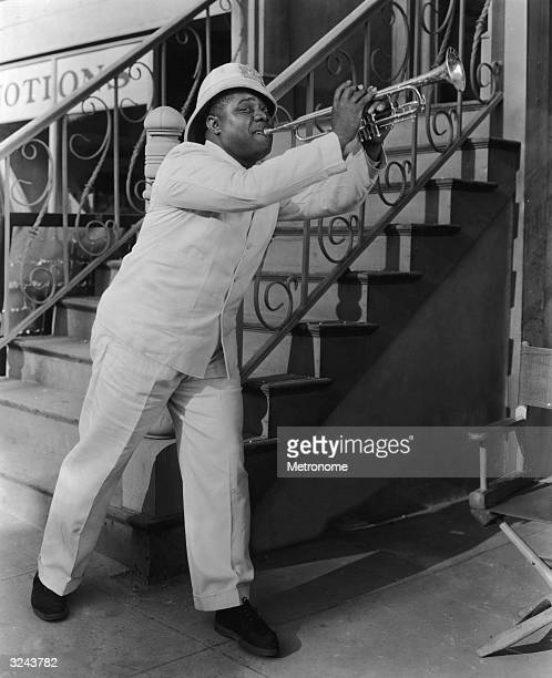 A fulllength image of American jazz musician Louis Armstrong playing the trumpet in front of a staircase in a promotional portrait for director A...