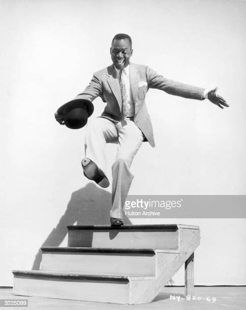 Fulllength image of American tap dancer and actor Bill 'Bojangles' Robinson dancing on a set of wooden steps in director Walter Lang's film 'Hooray...