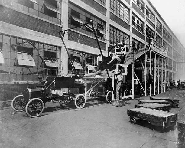 Full-length image of auto workers lowering the body...