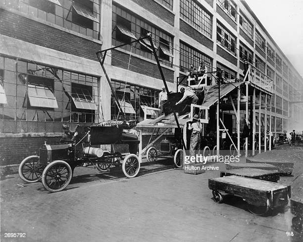 Fulllength image of auto workers lowering the body of a Model T onto its chassis on an assembly line ramp outdoors at the Ford Motor Company Highland...