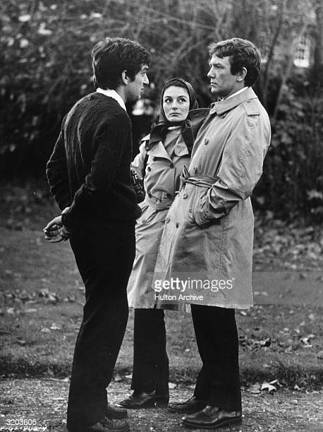 Fulllength image of British director Stephen Frears talking with French actor Anouk Aimee and her husband British actor Albert Finney outdoors on the...