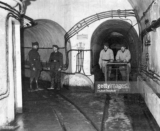 Fulllength image of French soldiers pushing a cart along tracks while heading towards an intersection within the fortifications of the Maginot Line...