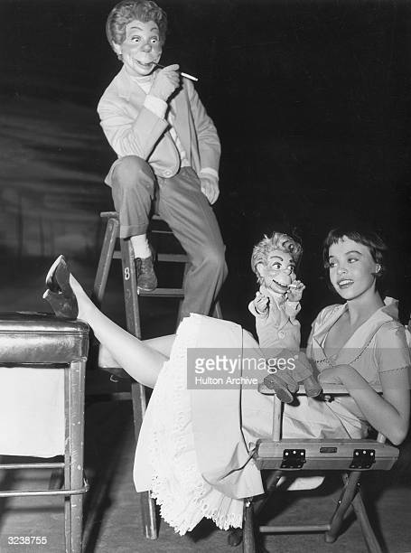 Fulllength image of Frenchborn actor and dancer Leslie Caron sitting in a director's chair posing with the puppet Carrot Top in her lap on the set of...