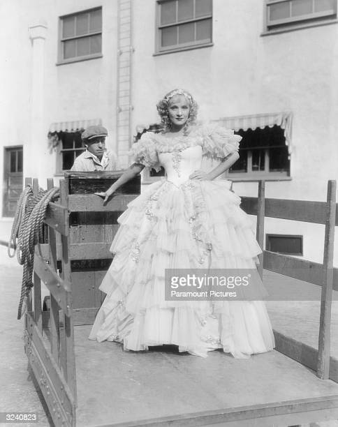 Fulllength image of German actor Marlene Dietrich in a ruffled gown by designer Travis Banton riding on a flatbed transport vehicle to protect her...