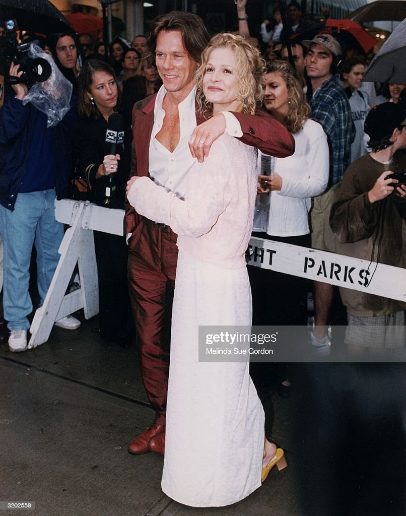 Full-length image of married American actors Kevin Bacon and Kyra Sedgwick attending the premiere of director John Turteltaub's film, 'Phenomenon,' in which Sedgwick starred, East Hampton, New York. Bacon wears a burnt orange silk suit. Sedgwick wears a long white dress.