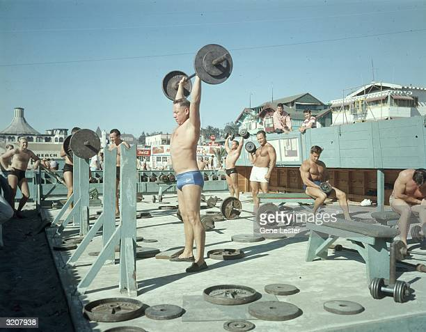 Fulllength image of men lifting weights in a special area walled off for weightlifting at Muscle Beach Santa Monica California Several Mr Americas...