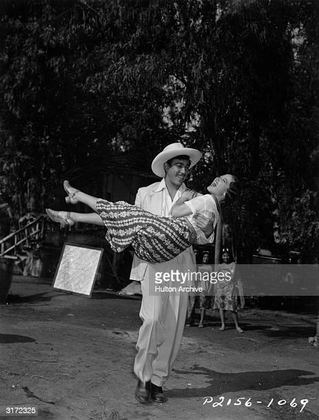 Fulllength image of Mexicanborn actor Anthony Quinn carrying American actor Dorothy Lamour down the South Sea Island street where director Victor...