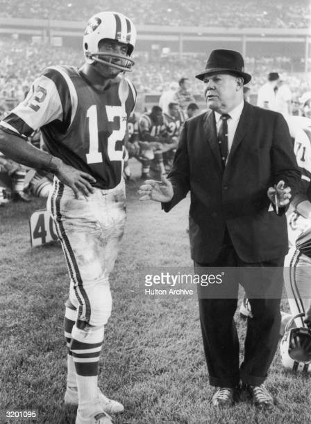 Fulllength image of New York Jets quarterback Joe Namath standing with his hands on his hips while listening to coach Weeb Ewbank during a game in...