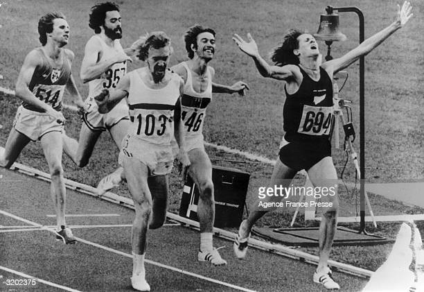 Fulllength image of New Zealander John Walker stretching his hands out after crossing the finish line to win the 1500 meter men's final during the...