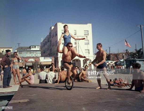 Fulllength image of student Judd Grant riding a unicycle while balancing his friend Carole Lee on his shoulders in front of onlookers at a beach in...